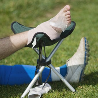 An athlete with a sprained foot applies RICE (rest/ice/compression/elevation) to the injured area.