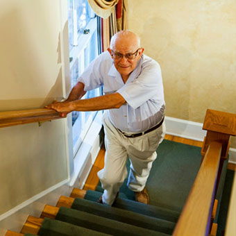 A male experiences hip pain while walking up the stairs.