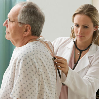 A female doctor examining a male patient.