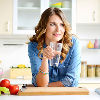 A woman drinking a glass of water.