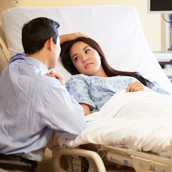 A husband comforting his wife in the hospital.
