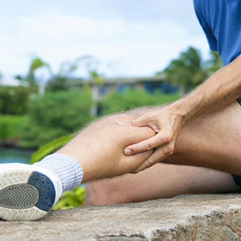A runner experiencing a muscle cramp in his calf.
