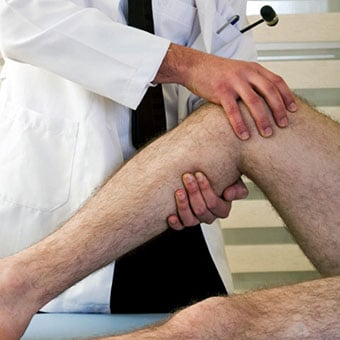 A doctor examining a male patient's leg.