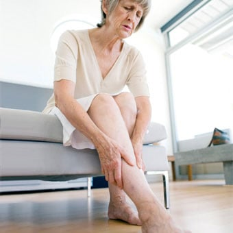 A senior woman rubbing her aching legs due to restless leg syndrome.