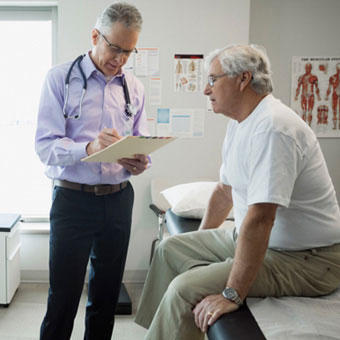 A doctor discussing symtoms with a male patient.