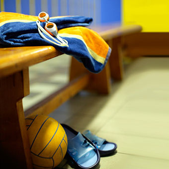 An empty locker room with a ball, towel, and flip-flop sandals.