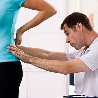 A doctor examines a patient's lower back.