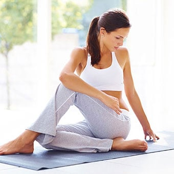 A woman performs stretching exercises for her back.
