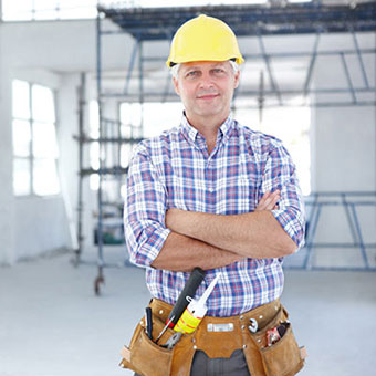 A male construction worker stands on site with his arms crossed.