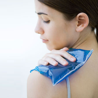 A woman placing an ice compress on her shoulder.