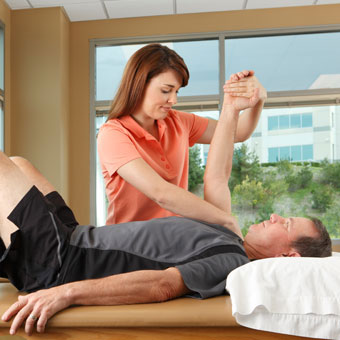 A physical therapist performing shoulder stretching exercises on a patient.