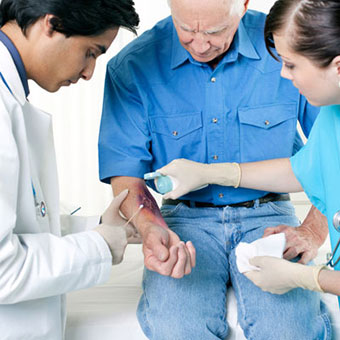 Doctor and nurse checking for staph on a male patient's arm.