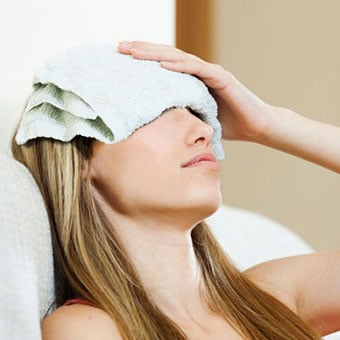 A woman uses a warm compress to relieve and treat a sty on her eye.