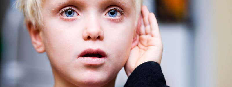 A man having difficulty hearing puts his hand to his ear.