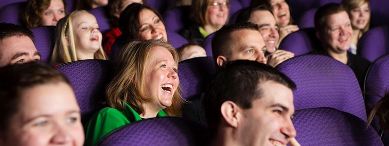 People in a movie theatre laughing.