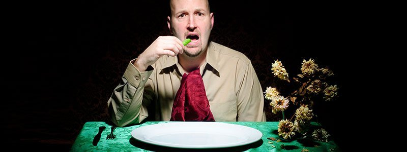 A man sitting in front of an empty plate.