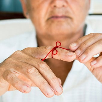 A close up of a red bow tied onto a man's finger.
