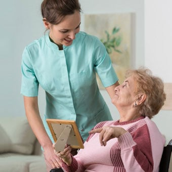 An elderly woman points at a picture frame.