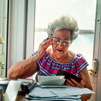 A senior woman struggling to work on finances.