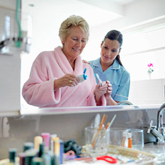 An nurse assists a senior woman brush her teeth.