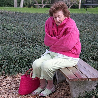 An elderly woman lost and shivering on a park bench.