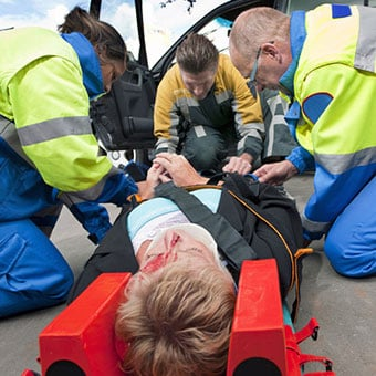Paramedics and a fireman strapping a wounded woman with a neck brace on a stretcher.