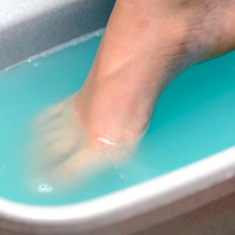 A woman soaks her foot.