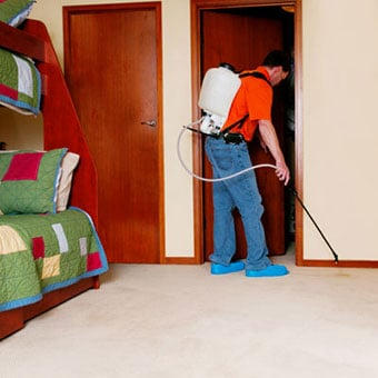 An exterminator sprays a bedroom for bedbugs.