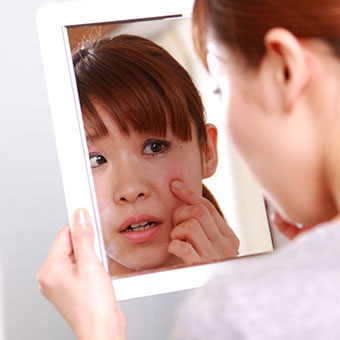 A woman examines a boil on her face in the mirror.
