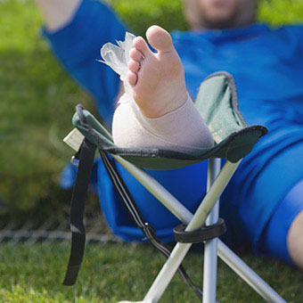 An injured soccer player following the RICE (rest, ice, compression, elevation) method to help decrease pain and swelling for his injury.