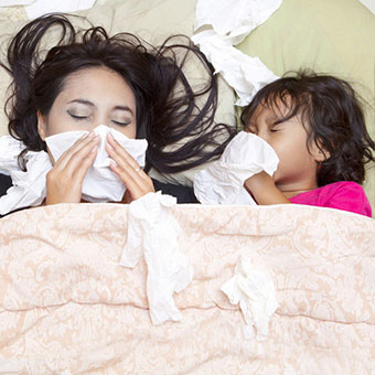 A mother and daughter in bed both suffering from bronchitis.