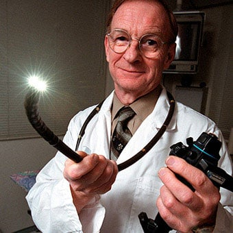 A doctor holds a colonoscope.