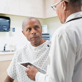 A doctor discusses colonscopy options and procedures with a patient.