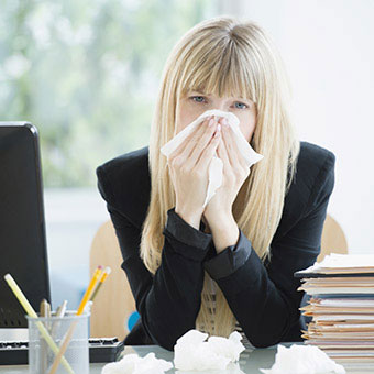 A woman sick at work blows her nose.