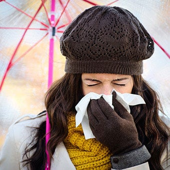 A woman with a cold blows her nose.