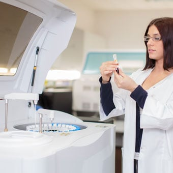 A lab technician tests blood samples in a blood analyzer machine.
