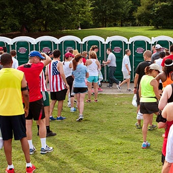 A line of runners wating in line to use portable toilets.