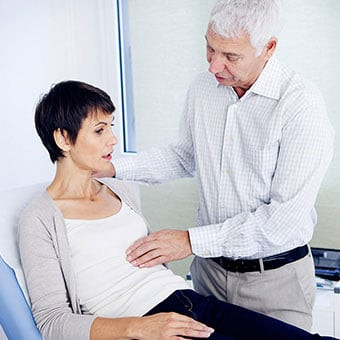 A doctor examines a female patient's abdominal area due to constipation.