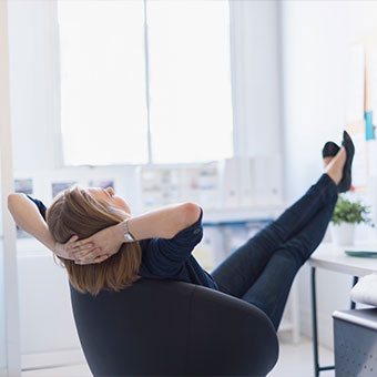 A woman relaxes with her feet up on her desk.
