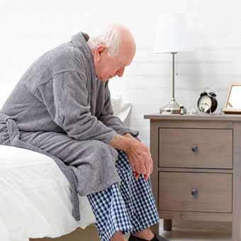 A senior man sitting in bed felling fatigued and confused.