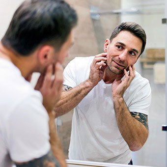 A man examines his face in the mirror.