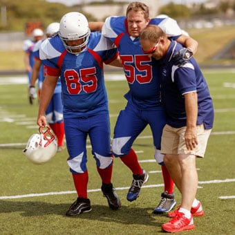 A football player gets help walking off the field after injuring his foot.