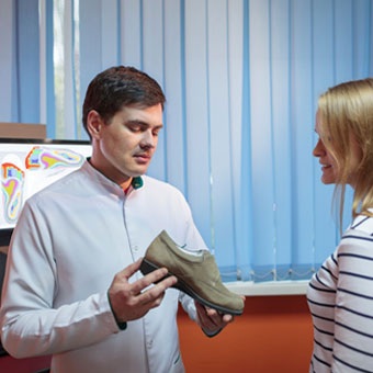 A woman consults with her podiatrist about proper shoes.