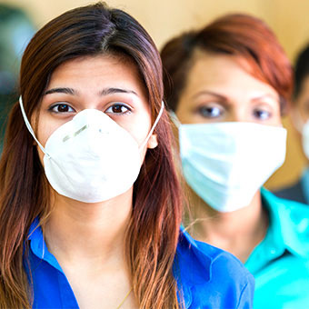 Two women wearing medical masks to avoid infection.