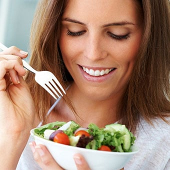 A woman eats an iron rich healthy salad.