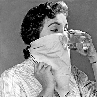 An woman drinks water through a napkin, an old wives tale hiccup remedy.