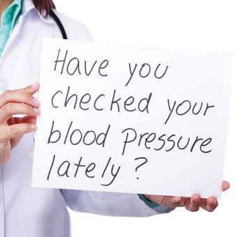 "Doctor holding a sign asking ""have you checked your blood pressure lately?"""