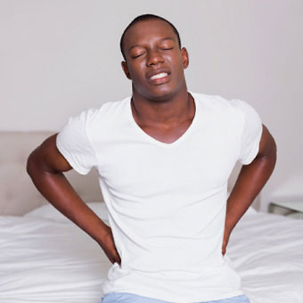 A man with back pain sits on a bed.
