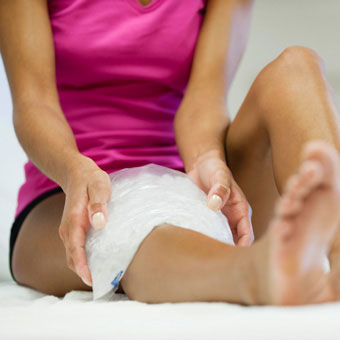 A female ices her knee to relieve pain.