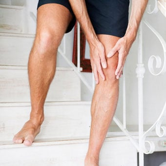 A man with knee pain has trouble walking down the stairs.